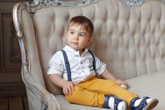 Menino muito bonito pequeno em calças amarelas e nos suspensórios que sentam-se na imagem de stock royalty free