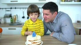 Menino muito bonito que comemora seu aniversário com um bolo & um pai feliz Feliz aniversario de 6 anos O rapaz pequeno funde par video estoque