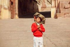 Menino não identificado que vem da escola com o schoolbag na cabeça, no humor cansado Fotos de Stock
