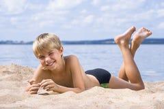 Menino na areia no seashore fotos de stock