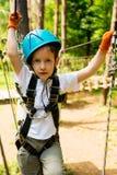 Menino na atividade de escalada no fio alto Forest Park Fotografia de Stock Royalty Free