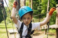 Menino na atividade de escalada no fio alto Forest Park Fotografia de Stock