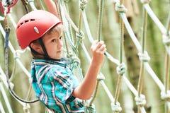 Menino na atividade de escalada no fio alto Forest Park Fotos de Stock