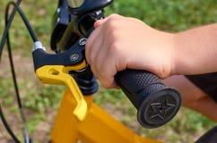 Menino na bicicleta amarela das crianças no parque, no leme com freios e nas mãos fotografia de stock