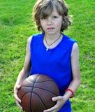 Menino na camisa azul com um basquetebol Fotos de Stock Royalty Free
