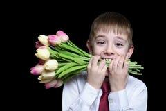 Menino na camisa e laço que guarda um ramalhete das tulipas nos dentes Isolado no fundo preto fotografia de stock