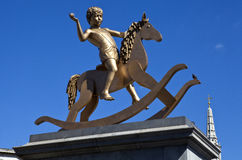 Menino na estátua do cavalo de balanço no quadrado de Trafalgar Foto de Stock