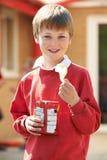 Menino na farda da escola que come a batata Chip In Playground foto de stock