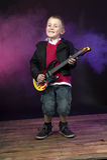 Menino na fase que joga a guitarra Fotografia de Stock Royalty Free