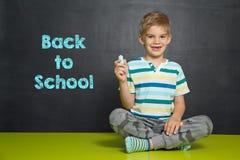 Menino na frente da administração da escola com texto DE VOLTA À ESCOLA Imagem de Stock Royalty Free
