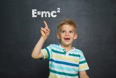 Menino na frente da administração da escola com texto Emc2 Fotografia de Stock