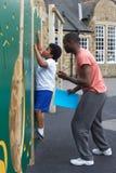 Menino na parede de escalada na classe da educação física da escola Imagens de Stock Royalty Free