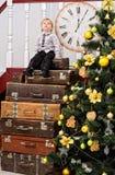 Menino na pilha das malas de viagem na árvore de Natal Imagens de Stock