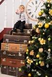 Menino na pilha das malas de viagem na árvore de Natal Fotografia de Stock Royalty Free