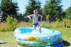 Menino na piscina. Imagens de Stock