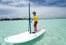 Menino na placa windsurfing. fotografia de stock royalty free