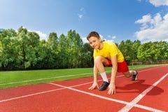 Menino na posição pronta sobre um joelho da curvatura a correr Imagens de Stock Royalty Free