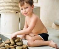 Menino na praia que constrói uma pirâmide Foto de Stock Royalty Free