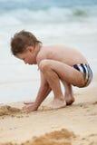 Menino na praia que joga na areia Fotografia de Stock