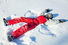Menino na roupa do inverno que faz o anjo da neve no parque do inverno fotos de stock