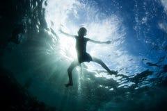 Menino na silhueta do oceano Fotografia de Stock