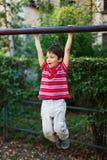 Menino na suspensão do parque Foto de Stock Royalty Free