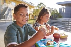 Menino na tabela elementar do almoço escolar que sorri à câmera foto de stock royalty free
