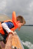Menino na veste de vida que inclina-se sobre trilhos do barco Fotografia de Stock Royalty Free
