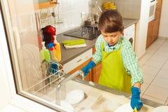 Menino nas luvas do avental e da borracha que fazem os pratos Fotografia de Stock