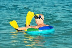 Menino nas máscaras e nas nadadas das aletas no mergulhador pequeno do mar fotografia de stock royalty free
