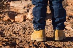 Menino nas sapatas amarelas que estão no deserto Fotografia de Stock Royalty Free