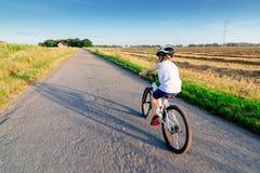 Menino no capacete branco que monta sua bicicleta fotografia de stock