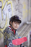 Menino no capacete com skate Fotos de Stock