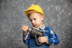 Menino no capacete de segurança com broca, chave de fenda à disposição foto de stock