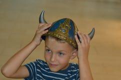 Menino no capacete de viquingue que olha de lado Imagem de Stock