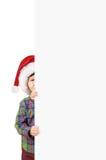 Menino no chapéu de Santa atrás de uma placa branca Fotografia de Stock Royalty Free
