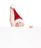 Menino no chapéu de Santa com placa Foto de Stock Royalty Free