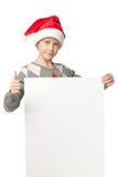 Menino no chapéu de Santa com placa em branco Fotografia de Stock Royalty Free
