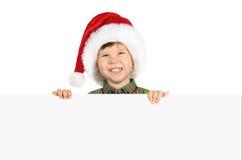 Menino no chapéu de Santa com placa em branco Fotos de Stock Royalty Free