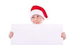 Menino no chapéu do Natal com uma placa Imagens de Stock Royalty Free