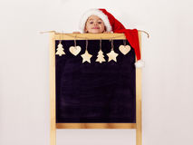Menino no chapéu do ` s de Santa com quadro-negro decorado Fotos de Stock