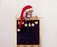 Menino no chapéu do ` s de Santa com quadro-negro decorado Imagem de Stock