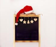 Menino no chapéu do ` s de Santa com quadro-negro decorado Fotografia de Stock Royalty Free