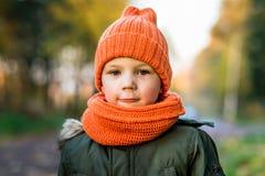 Menino no chapéu e no lenço alaranjados no parque no outono imagem de stock royalty free