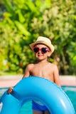 Menino no chapéu e nos óculos de sol que guardam o anel inflável imagem de stock royalty free