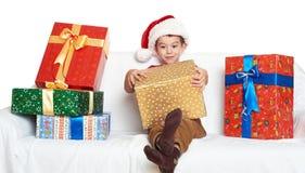 Menino no chapéu vermelho com caixas de presente - conceito do ajudante de Santa do feriado do Natal Imagem de Stock Royalty Free
