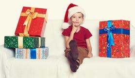 Menino no chapéu vermelho com caixas de presente - conceito do ajudante de Santa do feriado do Natal Imagens de Stock