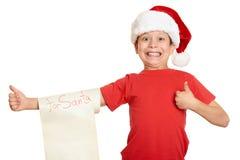 Menino no chapéu vermelho com letra longa do rolo com desejos a Santa Foto de Stock