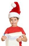 Menino no chapéu vermelho com letra longa do rolo com desejos a Santa Fotografia de Stock