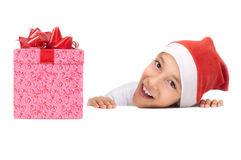 Menino no chapéu vermelho do Natal que prende uma caixa de presente Fotografia de Stock Royalty Free